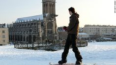 A man snowboards Sunday in Caen, France. Seventy-five French departments were under medium range (orange) alert for snow and ice Monday.