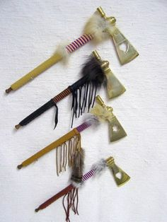 Cherokee Brass Hatchets with Pipes - These beautiful buckskin-wrapped brass hatchets are trimmed by hand with seed beads, horsehair, and feathers. The Large and Medium have working pipes, the Small is only a hatchet. The heart cutout, or weeping heart, was a trade item. Leather color and feathers will vary. Certificate of Authenticity included.  From $54.95.