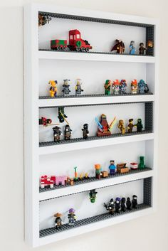 DIY Lego Minifiguren Vitrine This DIY Lego minifigure display case is easy to build with just boards and plywood! Add extra fun for kids with adhesive Lego tape that sticks to the walls and ceiling! This Lego minifig storage gets them out from underfo Wall Display Case, Display Shelves, Frame Display, Display Ideas, Shelving, Kid Toy Storage, Lego Storage, Storage Baskets, Wall Storage