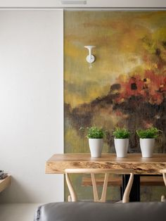 This looks like it might be canvas or fabric. love this colour added to the wall with the rough hewn edge of the table, wishbone chairs and trio of plants. very calm