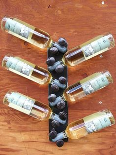 Wine rack that holds 6 bottles, railroad spikes welded to plate steel, clear-coated to show the natural colors.