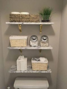 """Shop Marble Wall-Mounted Shelf 24"""". Smooth slab of Carrara-style white/grey marble showcases photos, art and objects of interest with natural cool. Levels out on industrial metal brackets with brass finish. For storage inspiration thats both practical and pretty, head to ."""
