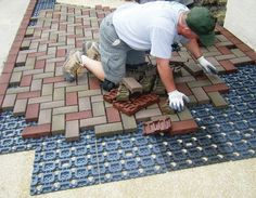 Azeks lightweight pavers are made from old tires and recycled plastic and are installed over a plastic grid system, which locks the pavers in place.