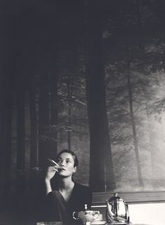 Black and white picture of pretty woman smoking with trees backdrop