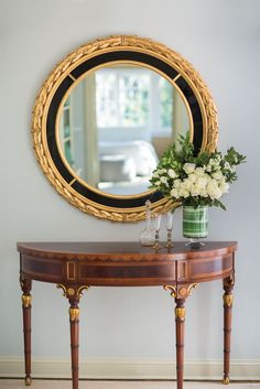 Luxurious interior with elegant inlaid Adams style console and Italian Neoclassic style mirror; luxury interiors inspiration; decorating ideas