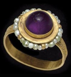 A BYZANTINE GOLD, PEARL AND AMETHYST FINGER RING CIRCA 6TH-7TH CENTURY A.D. The exterior of the strap hoop ornamented with braided plain wire filigree, the sides of the spool-shaped bezel with a ring of pearls threaded on a wire and secured by small loops, bands of beaded wire above and below, the bezel set with a circular cabochon amethyst.