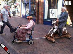 Een oude dame op een scooter met een trailer ... op de trailer: een oude man in een pak zittend op een driedelige swing pony