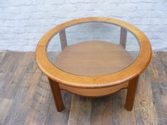 A Genuine G Plan large round Teak coffee table with glass inset and shelf beneath.
