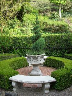 Looks like a baptismal fount planted with flowers and topiary shrub . . .Beautiful garden feature . . .