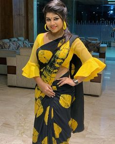 In a yellow and black color printed saree and pleated bell sleeve blouse design New Saree Blouse Designs, Blouse Designs High Neck, Simple Blouse Designs, Stylish Blouse Design, Bridal Blouse Designs, Sleeves Designs For Dresses, Sleeve Designs, Dress Designs, Girl Sleeves