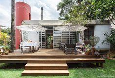Jardim de casa modernista tem área com mesa para refeição e sofás no deck de madeira.