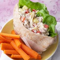 Twisted Tuna Salad   1  2 ounce can chunk white tuna (water-pack), drained - 1/3 cup bottled creamy Italian salad dressing,1/3    cup finely chopped fresh or drained, canned pineapple, 1/4 cup finely chopped red sweet pepper, 4 - 8     Boston lettuce leaves, 2 pita bread rounds, halved