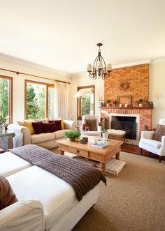 Sala de estar com lareira em casa de campo. Decoração prioriza revestimentos naturais e elementos artesanais para criar ambiente aconchegante. Projeto de design de interiores em Campos do Jordão.