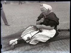 Woman in traditional costume mending fishing nets (Scheveningen)