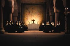 Nuns praying in old church lit by candlelight