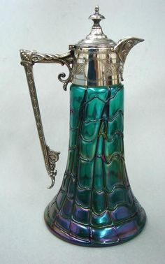 Stunning Art Nouveau claret jug with silver plated top and handle, beautiful iridescent art glass base, with blue and purple colours.  Some research on the internet  suggests that these iridescent glass bases were often made by Loetz or Palme Konig: