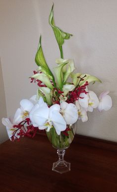 Beautiful Orchids accented by green callas .www.racheljeansevents.com