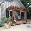 This beautiful pergola is made from 100% Chinese cedar. It lets vines and crawling roses turn your patio into a naturally shaded oasis. Sculptured beams criss-cross both directions and give it strength as well as flair. The 4 uprights are made from Chinese cedar,  on a side. And Backyard Discovery`s patent-pending decorative foot covers hide unique anchors that keep the pergola firmly secured to the ground or patio. The inside dimensions are with a headroom, so all your patio furniture w...