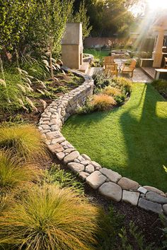 via houzz, design by Sally Stoik Landscape Architect. Stone paved patio, grass, and retaining wall taming backyard slope. Ideal landscaping.