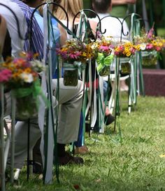 mason jars with wildflowers tied with ribbon from shepherd hooks for aisle wedding decorations