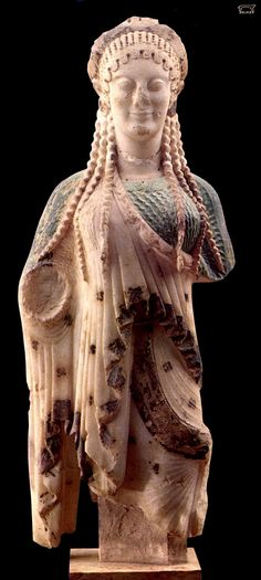 ARCHAIC: Kore from the acropolis, Athens. c. 510 BCE.  the elaborate clothing of the kore figure hides the body underneath. The artist's focus is directed to the elaborate patterns of the drapery and hair.