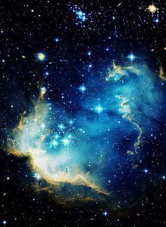 """Mariano Minguela Merino NGC 602 es un cúmulo abierto joven, brillante de estrellas ubicadas en la Pequeña Nube de Magallanes (SMC), una galaxia satélite de la Vía Láctea. Radiación y ondas de choque de las estrellas han empujado lejos mucho del encendedor de gas circundante y polvo que componen la nebulosa conocida como N90, y esto a su vez ha provocado la formación de nuevas estrellas en las crestas (o """"trompas de elefante"""") de la nebulosa."""