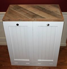This is a custom made Dual Tilt Out Trash Bin. It comes in the color white. The top is made from rustic reclaimed pallet wood. Each door tilts out