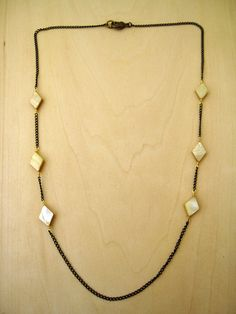 3 shell beads wrapped symmetrically on opposite sides with an 22 inch long oxidized brass chain with lobster clasp