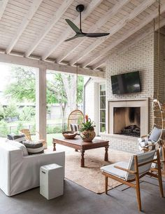 Covered patio features a living space boasts a white slipcovered sofa  facing a teak coffee table ...