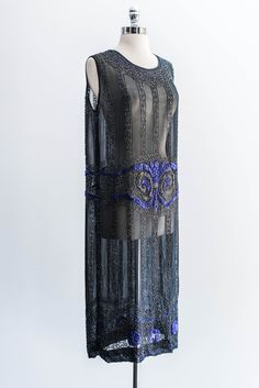 a sheer black 1920s chiffon flapper dress with blue and black art deco beading design.