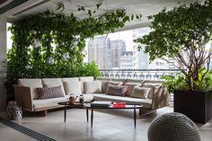 Decoração de apartamento com área verde. Na varanda cores neutras, sofá branco com almofadas, mesa de centro com livro e e adornos e plantas.