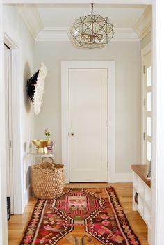 Boho foyer features greige walls over honey oak hardwood floors layered with a colorful Kilim rug ...