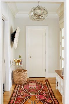 Boho foyer features greige walls over honey oak hardwood floors layered with a colorful Kilim rug ...