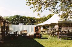 Boho Camp Wedding I like the way they set up the lights, tent, and backdrop. Pinned for setup, don't need all the vintage mismatched furniture though