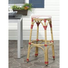 Raise a glass to country and coastal decorating with the red and white Kipnuk indoor-outdoor barstool from Safavieh. A colorful addition to a kitchen or patio bar, the pretty Kipnuk is inspired by classic European bistro stools and crafted of white PE wicker and aluminum faux bamboo for easy care.