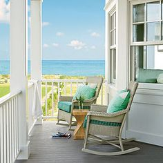 Seaside resort with wicker rocking chairs and aqua pillows.