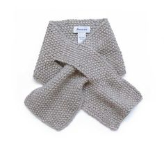 This scarf features a moss stitch and an opening on the front to make the fit perfect for anyone.