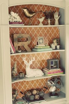 put contact paper, wallpaper pieces, or fabric against cork board in size to fit the back of each shelf. Then you're able to change it out with seasons, decorations, etc!!