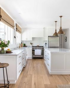 Bright white kitchen with brass accents and warm wood floors.