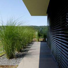Minimalistische Gartengestaltung am Hang mit Wasserbecken aus Cortenstahl und Feuerstelle |