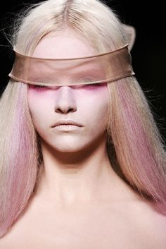 Vibrant pink eye makeup and center part blonde hair with sublte pink highlights.