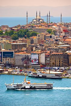 The Sultan Ahmed Mosque (Sultanahmet Camii or Blue Mosque 1609 to 1616 ) on Sarayburnu or Seraglio Point with a ferry and the banks of the Golden Horn in the foreground, Istanbul Turkey.