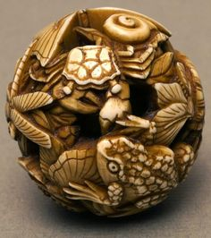 Ivory netsuke ball carved with dragonflies, butterflies, a tortoise, a frog,...  -  boltonmuseums.org.uk