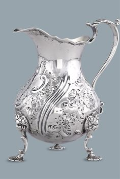 This exquisite silver cream pitcher was crafted by English silversmith Francis David Dexter. The three-footed design is encased in Rococo-style flourishes and hand-chased floral accents. Both beautiful and functional, it is a charming example of Victorian-era English silver ~ 19th Century, England ~ M.S. Rau Antiques