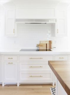 Studio McGee. Christopher Scott custom Cabinetry painted BM Chantilly Lace. Like flat panel cabinet style but different hardware, subway tile, wood floor and counter. Mix of modern clean lines and traditional.