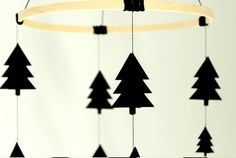 Bring the forest to your childs room all year around. This lovely Scandinavian tree mobile will be the perfect accent for any modern nursery or kids room.  Made of 100 lbs heavy cardstock, acid and lining free. The main hoop is 9 in diameter. The trees are 3D (showed in picture number 2) and the mobile has 18 shapes in total. Two strings of four elements and another two with five. There are three different sizes for the trees and they are randomly arranged, making of each mobile one of a…