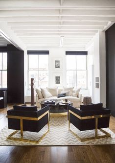 gold base and black upholstery arm chairs, black and white, dark wood flooring, exposed beams: