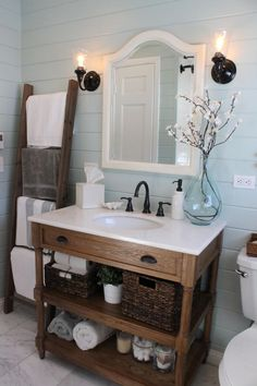 great sink with shelves instead of drawers, black faucet, light blue walls, black sconces on either side of mirror. LOVE this bathroom!.