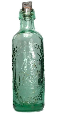 A beautifully embossed plain screw cap cylinder mineral water from the Greenock Apothecaries. The trade mark features the Scottish Inventor James Watt sat in a chair. This bottle was recovered from the floor of a harbour near Helensburgh by shellfish divers in the 1980s.