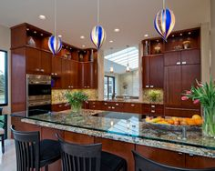 Warm wood tone cabinets, granite counters w custom glass tier, stainless appliances with blue accent pendants Coastal Va Magazine's Best Kitchen & Bathroom Remodeler #dogoodwork www.jimhicks.com